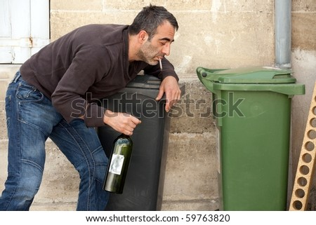 very drunk man smoking cigarette on trashcan - stock photo