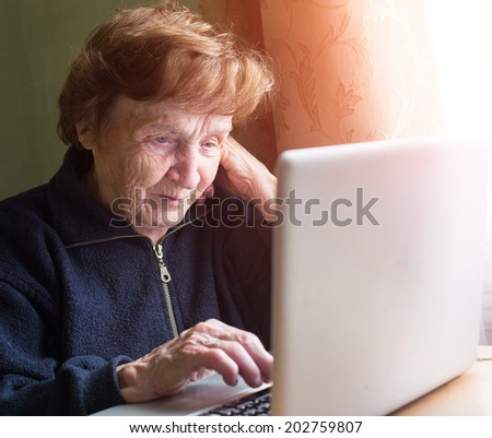 Very elderly woman sing laptop computer at home. - stock photo