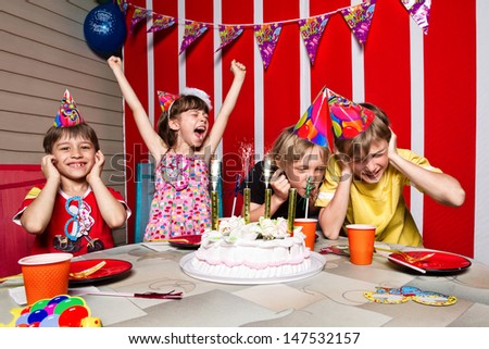 Very emotional little girl rejoice  in her birthday round about her friends - stock photo