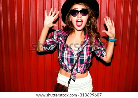 Very emotional portrait of Fashion stylish portrait of pretty young hipster blonde woman,going crazy,elegant black hat,soft colors,cool crazy teen girl.Red urban wall background.surprised girl  - stock photo