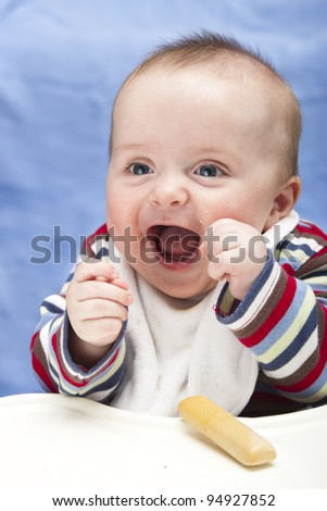 Very excited, messy 6 month old boy - stock photo