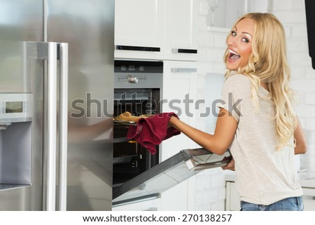 very expressive commercial woman , with happy face , cooking some food with oven , in her kitchen. - stock photo