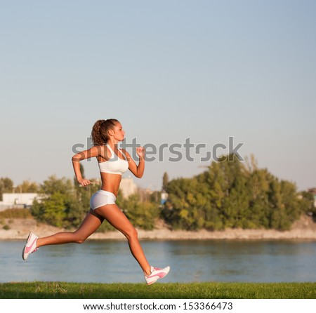 Very fit gorgeous young brunette woman exercising outdoors. - stock photo