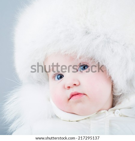 Very funny baby in a white snow suit and big fur hat - stock photo