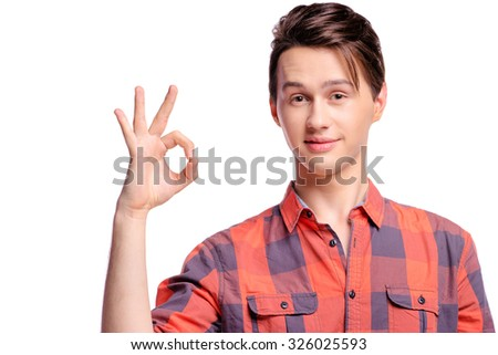 Very good! Studio portrait of happy handsome young man showing okey sign with fingers. Isolated on white. - stock photo