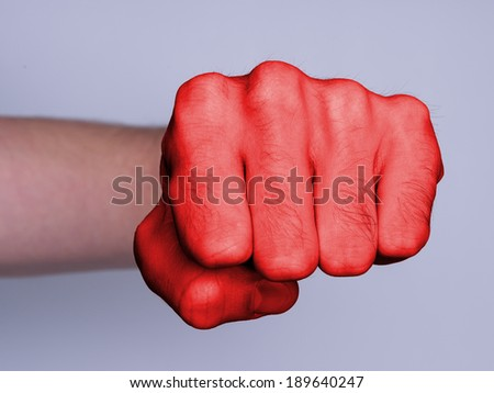 Very hairy knuckles from the fist of a man punching, red skin - stock photo