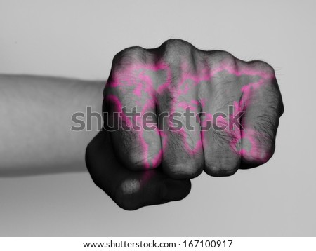 Very hairy knuckles from the fist of a man punching, world map neon print - stock photo