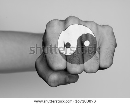 Very hairy knuckles from the fist of a man punching, yin yang print - stock photo