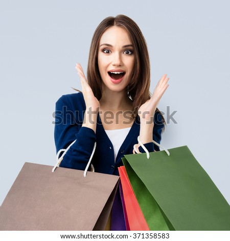 Very happy beautiful young woman in casual clothing with shopping bags - stock photo
