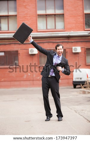 very happy businessman waving his briefcase on the street - stock photo