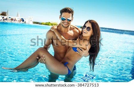 Very happy couple wearing sunglasses enjoy each other in swimming pool. Man holding woman on hands - stock photo
