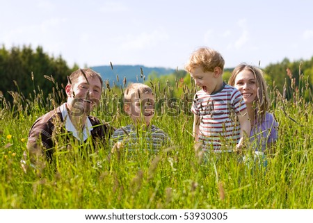 Very happy family with two kids sitting in a  meadow in the summer sun in front of a forest and hills, they are nearly hidden by the high grass, very peaceful scene - stock photo