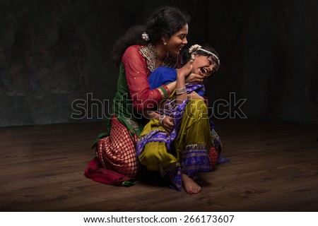 very happy Indian family , mom plays with her daughter. dressed in national costumes - stock photo