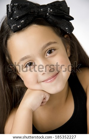 Very happy little girl resting fave on her hand, black ribbon in her hair - stock photo