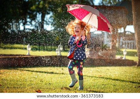 Very Happy Little girl with umbrella playing in the rain. Kids play outdoors by rainy weather in fall.  - stock photo