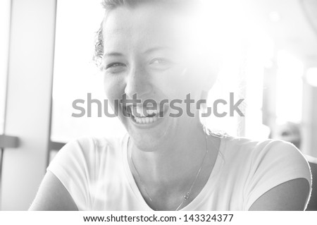 very happy woman is sitting in cafe and looking at camera - stock photo