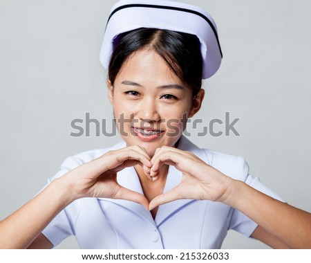 Very happy young Asian nurse show heart hand sign on gray background - stock photo