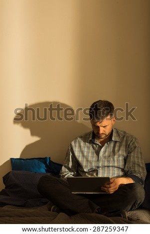 Very lonely man is sitting alone in his empty apartment - stock photo