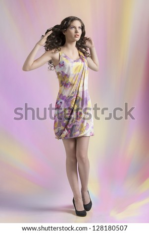 very nice and young girl standing on color background and wearing a spring colorful dress - stock photo
