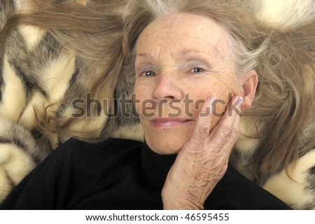 Very Nice Image of a senior Glamour model On Fur - stock photo