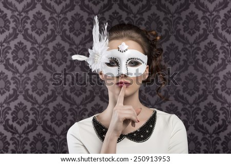 very nice young woman in white with elegant dress and mask with feather on vintage background - stock photo