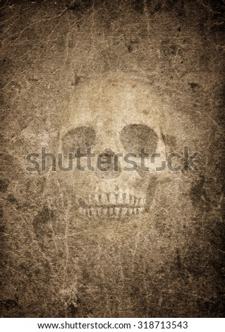 Very old burnt grunge textured paper with human skull - stock photo