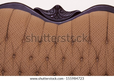 Very old couch with patterned fabric and beautiful and ornate wood trim - stock photo