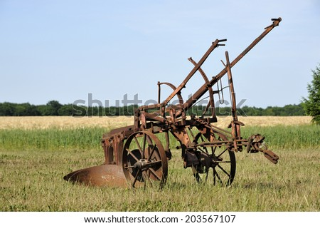 Very old farm equipment in large field - stock photo