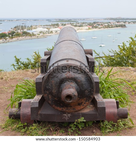 Very old rusted canon pointing at a bay, Caribbean - stock photo