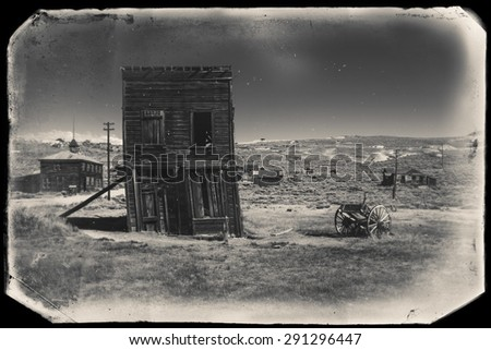 Very old sepia vintage photo with abandoned and crooked western city building built during gold rush, Bodie - stock photo