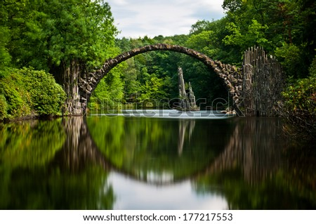 Very old stone bridge over the quiet lake with its reflection in the water, long exposure - stock photo