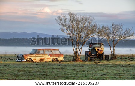 Very old vintage and rusty truck and car sit undisturbed in a field and catch the first rays of sunlight on a  misty foggy frosty morning in the country.  Richmond NSW Australia - stock photo