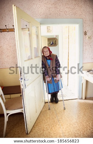 Very old woman is standing by the door with crutches at her country style house - stock photo