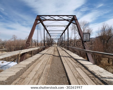 Very old wooden bridge in the rural midwestern countryside. - stock photo