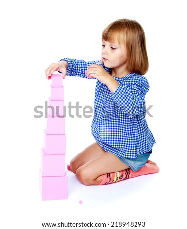 Very passionate little girl collects Montessori pyramid.Education concept happy child. - stock photo