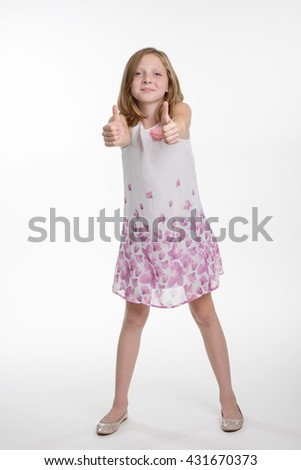 Very positive child shows OK gestures. Warm attitude of a little girl. Cute kid on the white background in the studio. - stock photo