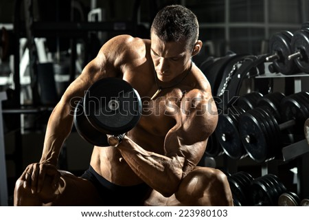 very power athletic guy bodybuilder ,  execute exercise with  dumbbells, in dark gym - stock photo