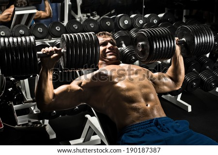 very power athletic guy ,  execute exercise press with  dumbbells, workout  in sport hall - stock photo