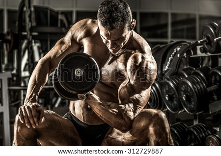 very power athletic guy ,  execute exercise with  dumbbells, on bkack background, horizontal photo - stock photo