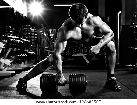 very power athletic guy ,  execute  traction with  dumbbells, exercise on broadest muscle of back, in sport hall,  black-and-white photo - stock photo