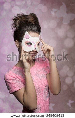 very pretty brunette woman posing in carnival shoot masquerade with lovely kitten mask. Wearing pink stylish portrait, creative hair-style and smiling  - stock photo