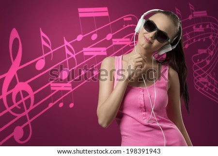 very pretty funny girl with pink singlet and long brown ponytail listening music with headphones  - stock photo