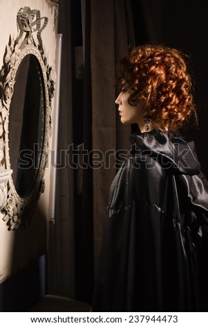 Very pretty woman vamp looking at her reflection in mirror - stock photo