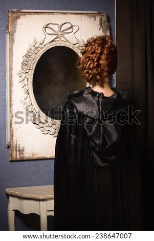 Very pretty woman vamp looking at mirror - stock photo