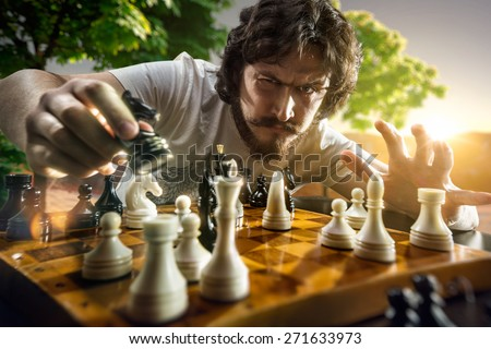 Very serious man is playing the chess - stock photo