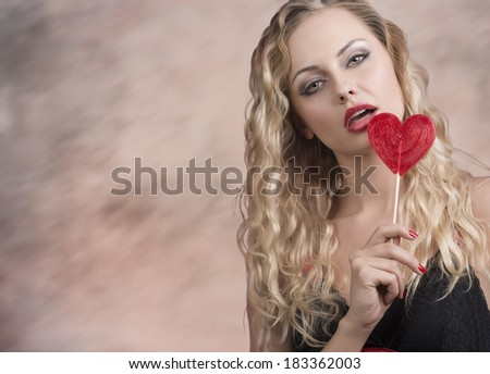 very sexy blonde lady posing with sensual expression and wavy blonde hair, taking red heart shaped lollipop and wearing black dress   - stock photo