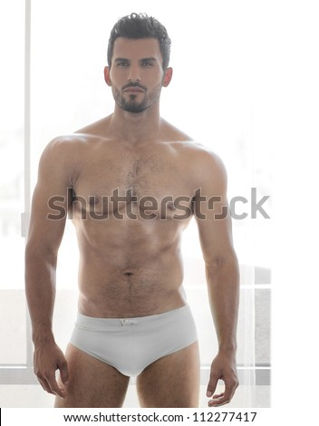 Very sexy young male muscular model in white underwear in front of window - stock photo