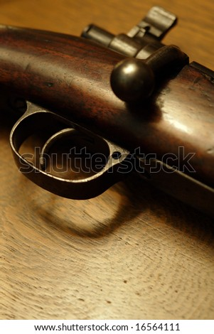 Very shallow depth of field image of the trigger of an old shotgun.  Focus is on the tip of the trigger. - stock photo