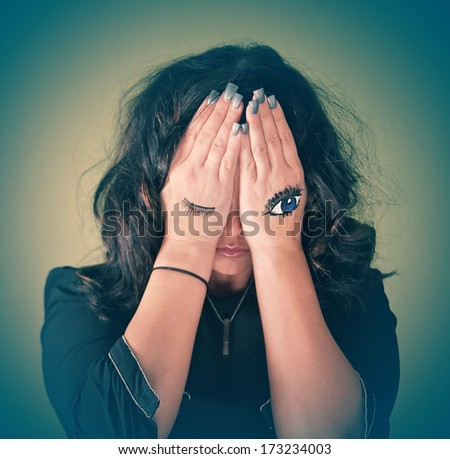 very shallow depth of field shot of a depressed person (focus on the painted eye only) - stock photo