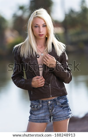 Very skinny model with blonde straight hair posing outdoors - stock photo